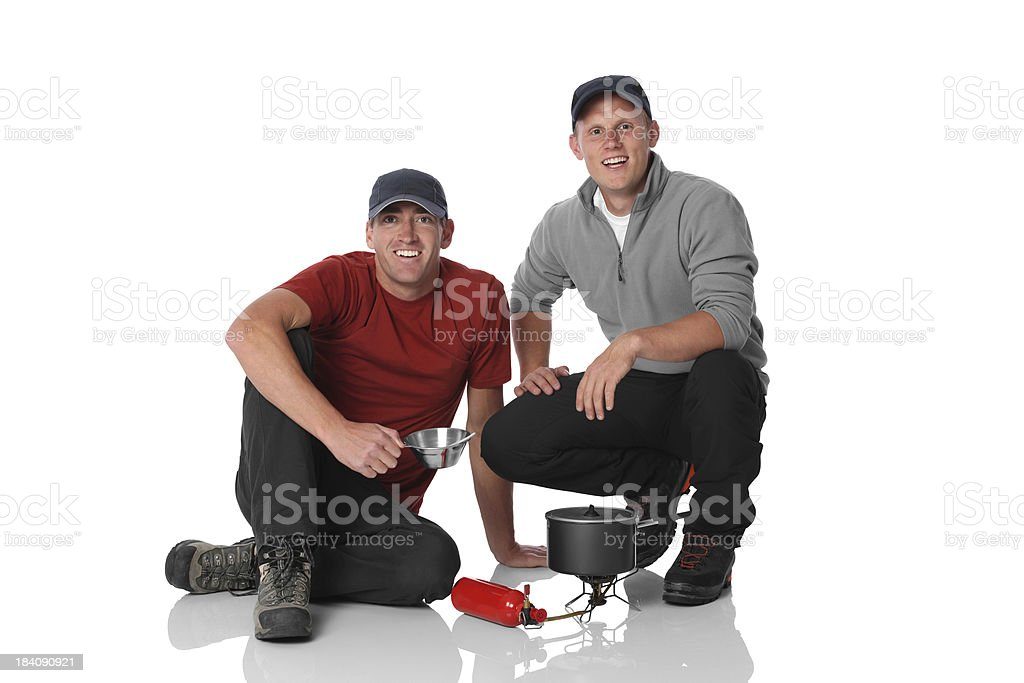 Two hikers cooking food on camping stove royalty-free stock photo