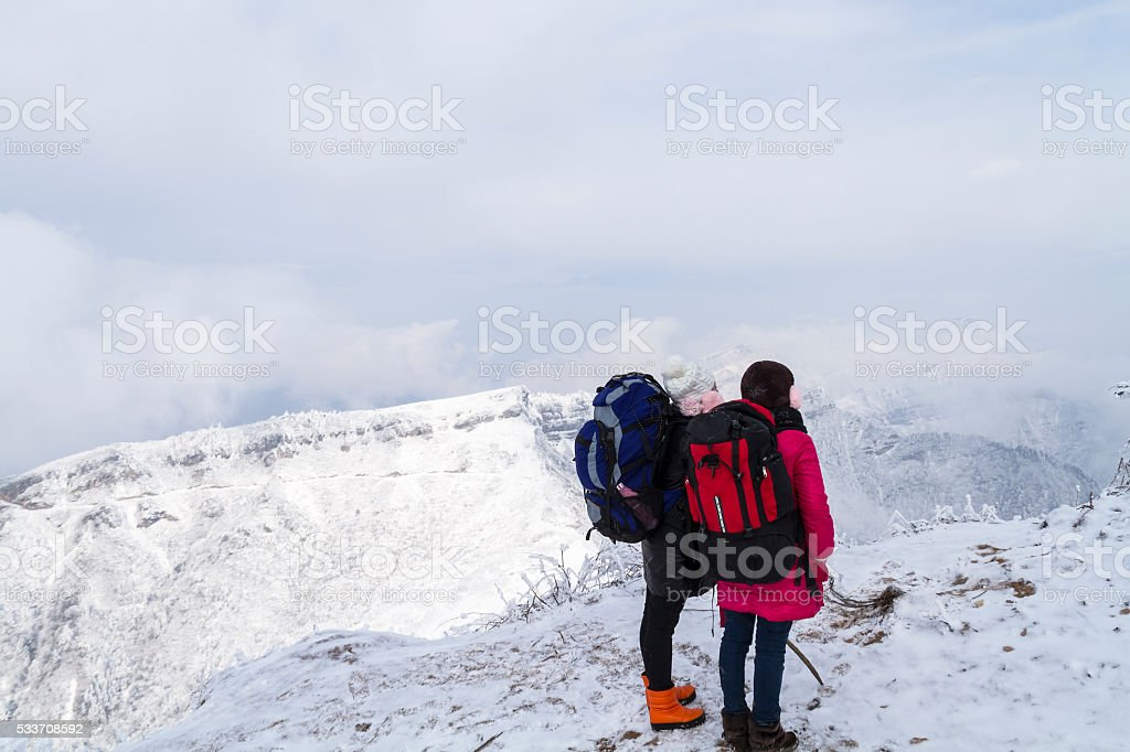 Two Hikers in Mountain Niubeishan Looking at View stock photo