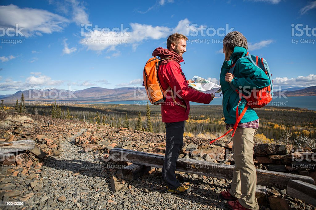 Two hikers looking at map for directions stock photo