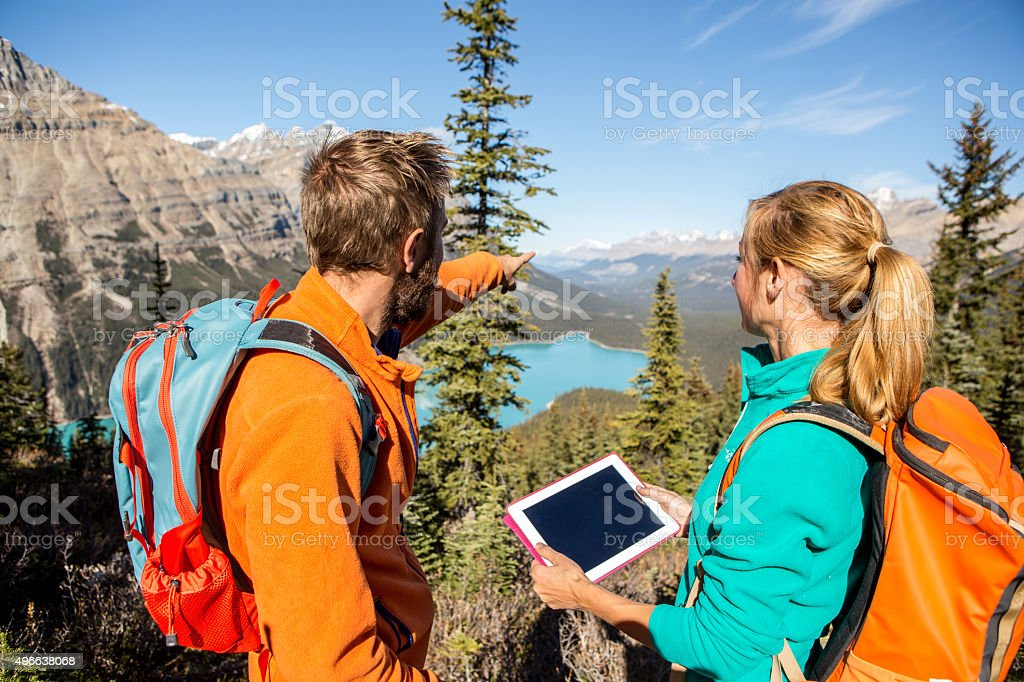 Two hikers looking for directions on digital map stock photo