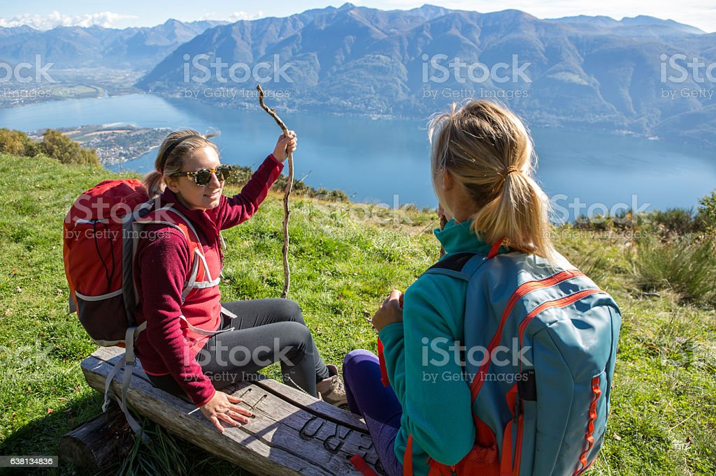 Two hikers on mountain top contemplating landscape stock photo