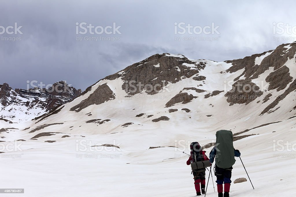 Two hikers on snowy plateau before storm royalty-free stock photo