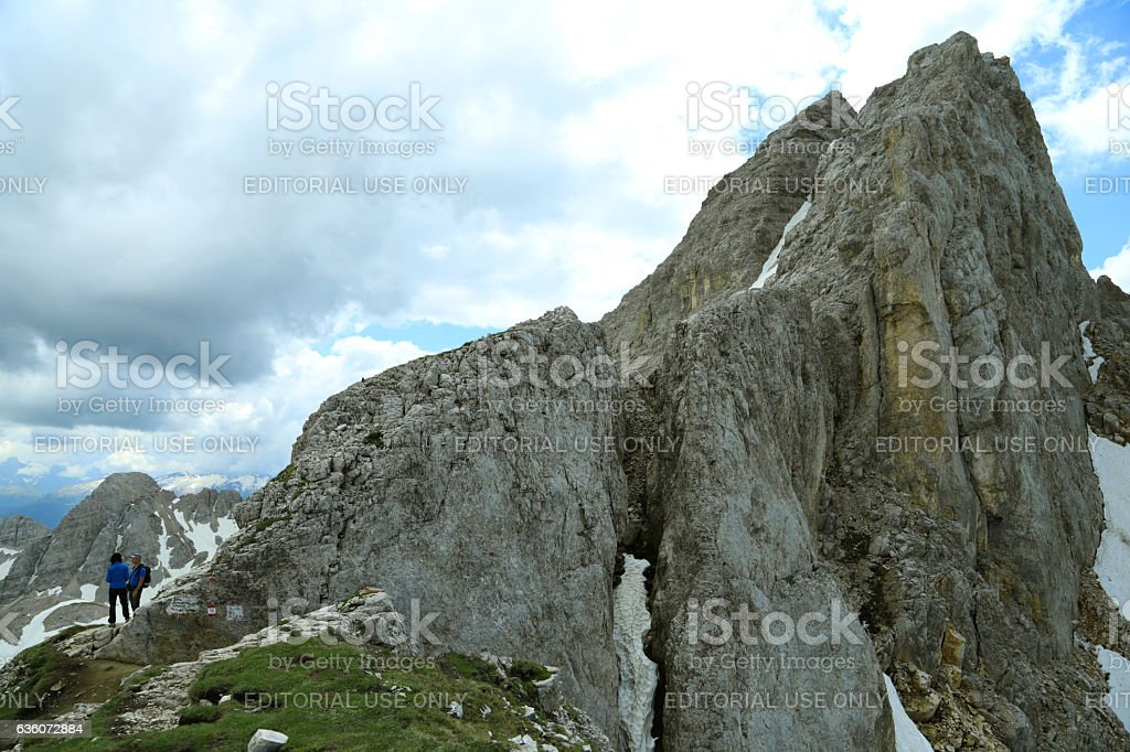 Two hikers standing near a peak, in Latemar mountain stock photo