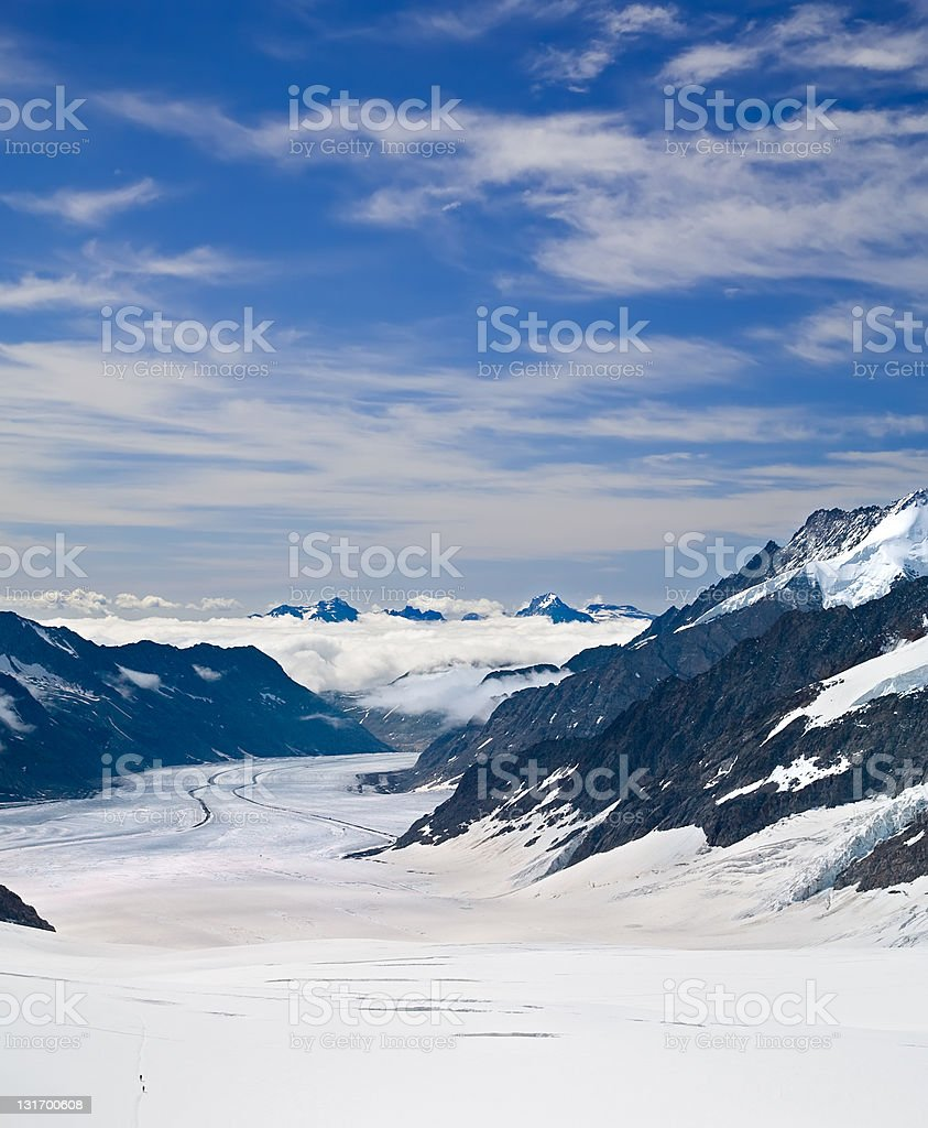 Two Hikers Walking Towards Aletsch Glacier in the Alps, Switzerland royalty-free stock photo