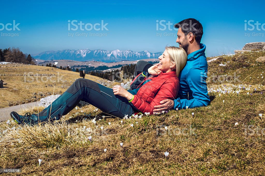 Two hikers with backpack resting on the mountain top stock photo