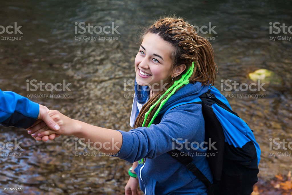 Two Hikers young Man and Smiling Woman holding hands stock photo
