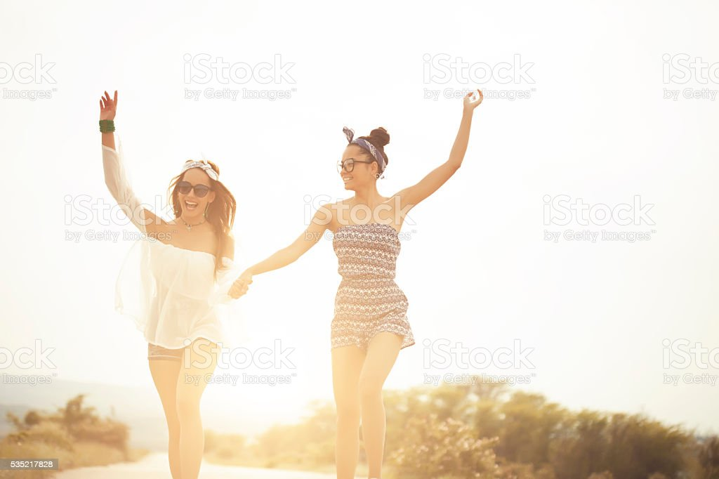 Two hippie women holding hands and dancing on the road stock photo
