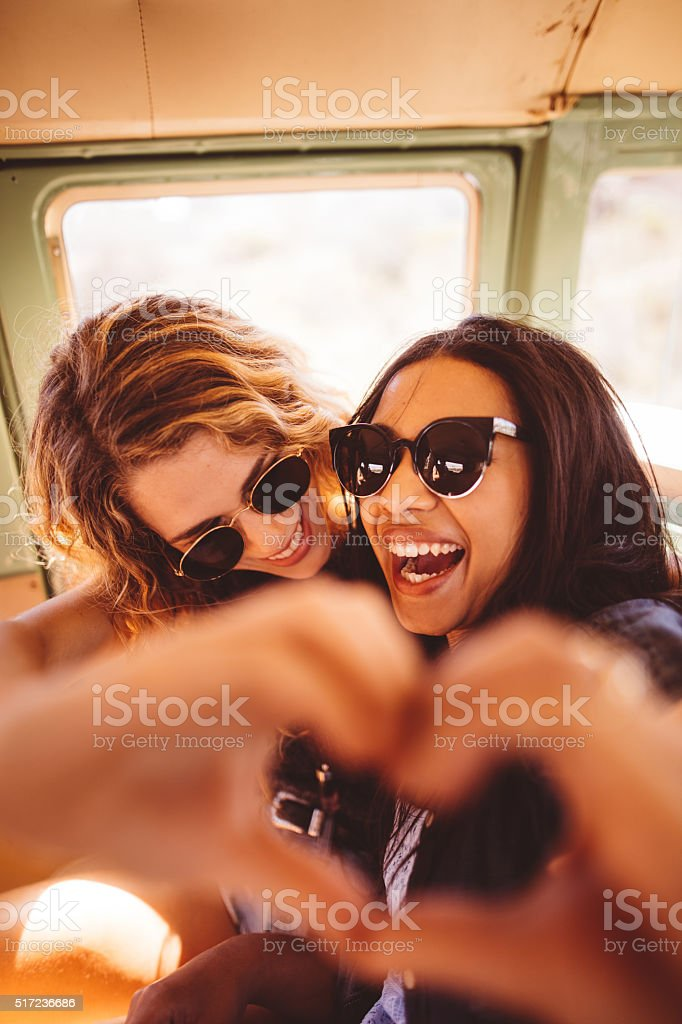 Two Hipster Girls Posing for Photo Making Hand Heart stock photo