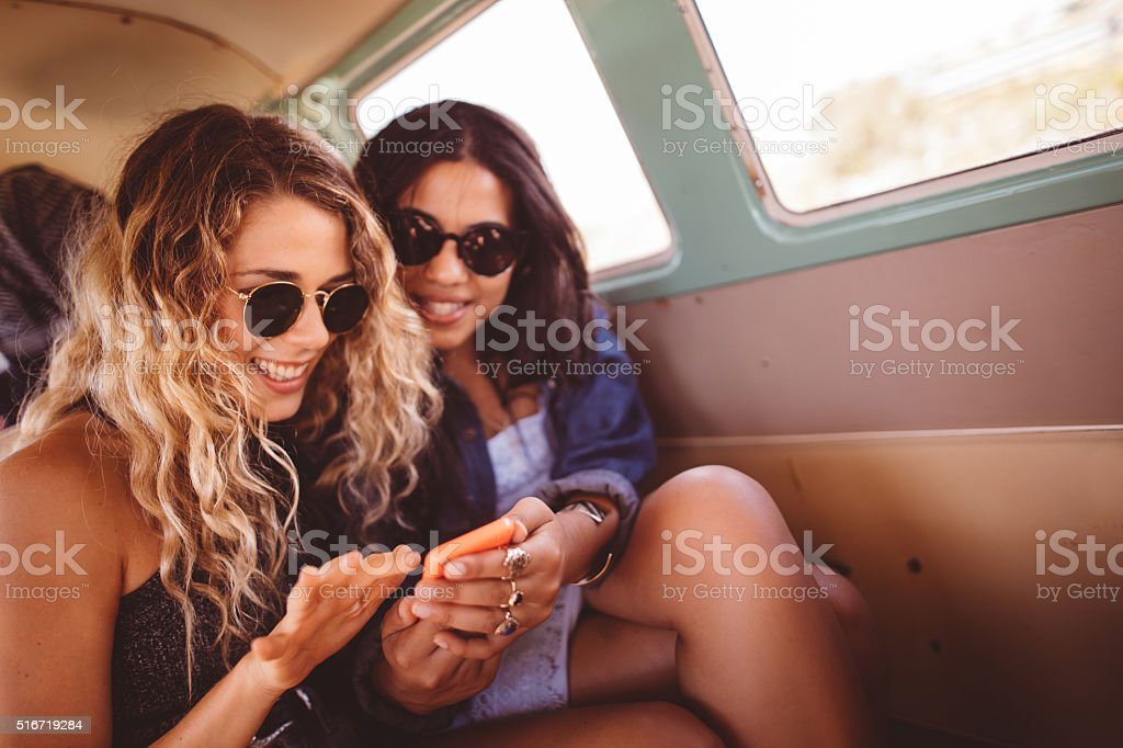 Two Hipster Girls Sitting Together in van Looking at Phone stock photo