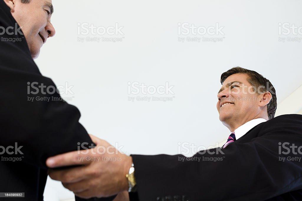 Two hispanic businessmen shaking hands stock photo