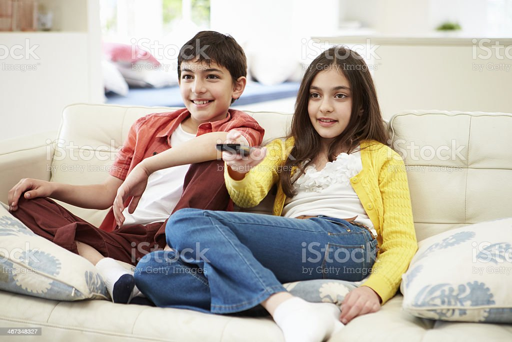 Two Hispanic Children Sitting On Sofa Watching TV Together stock photo