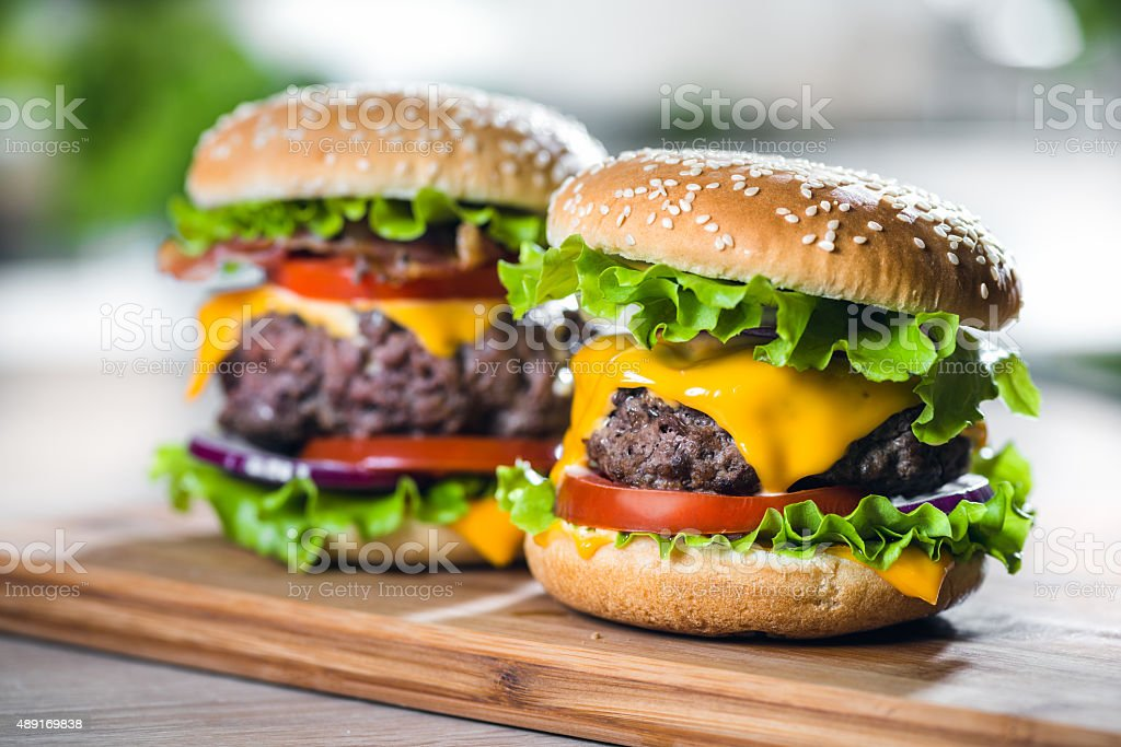Two Home Made Huge Cheeseburger on oak chopping board stock photo