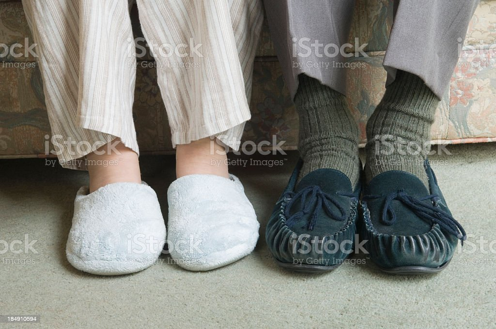 Two home slippers worn by people sitting on the couch royalty-free stock photo