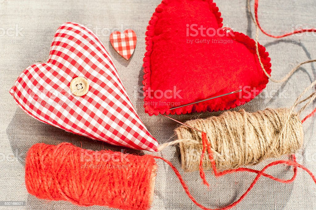 Two homemade sewed red cotton love hearts. Closeup. stock photo