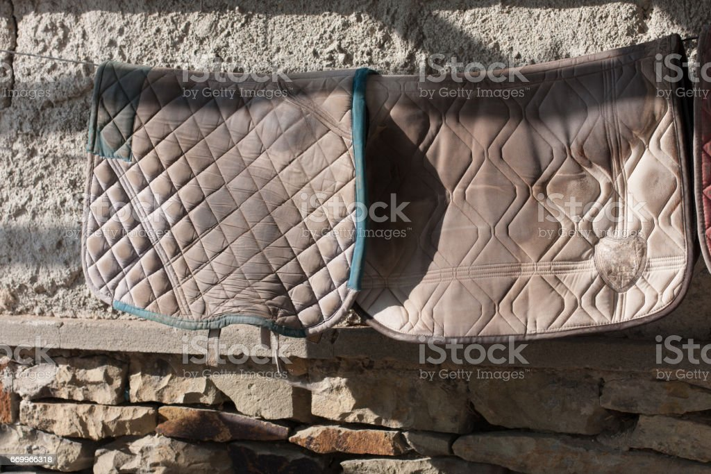 Two horse blankets hanging on clothesline stock photo