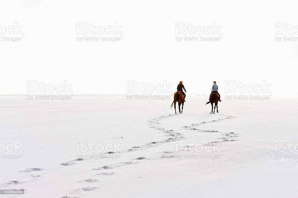 Two horseriders leave hoofprints in the sand on winter day stock photo