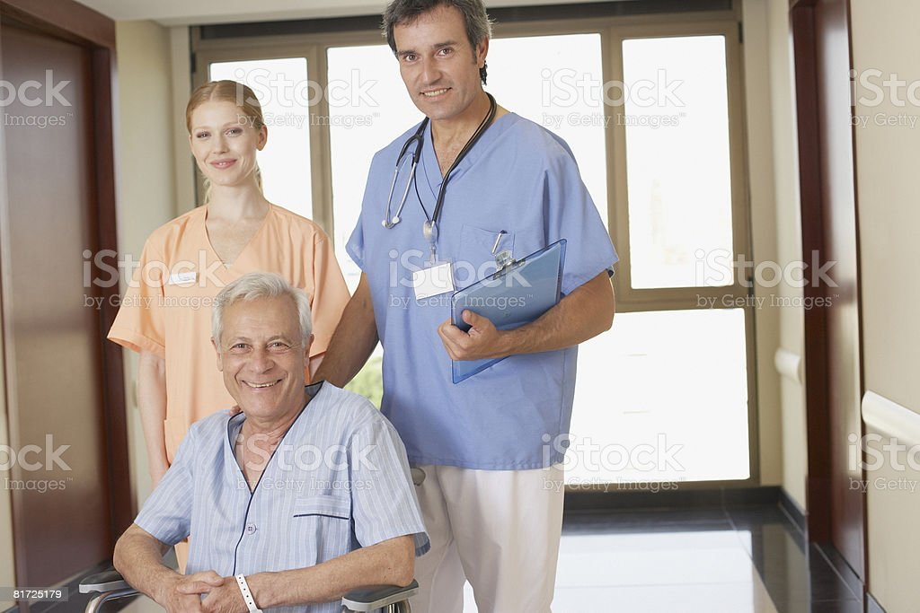 Two hospital workers in corridor with senior patient in wheelchair smiling royalty-free stock photo