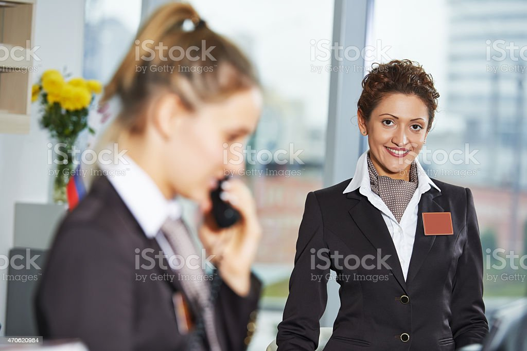Two hotel reception workers at front desk stock photo