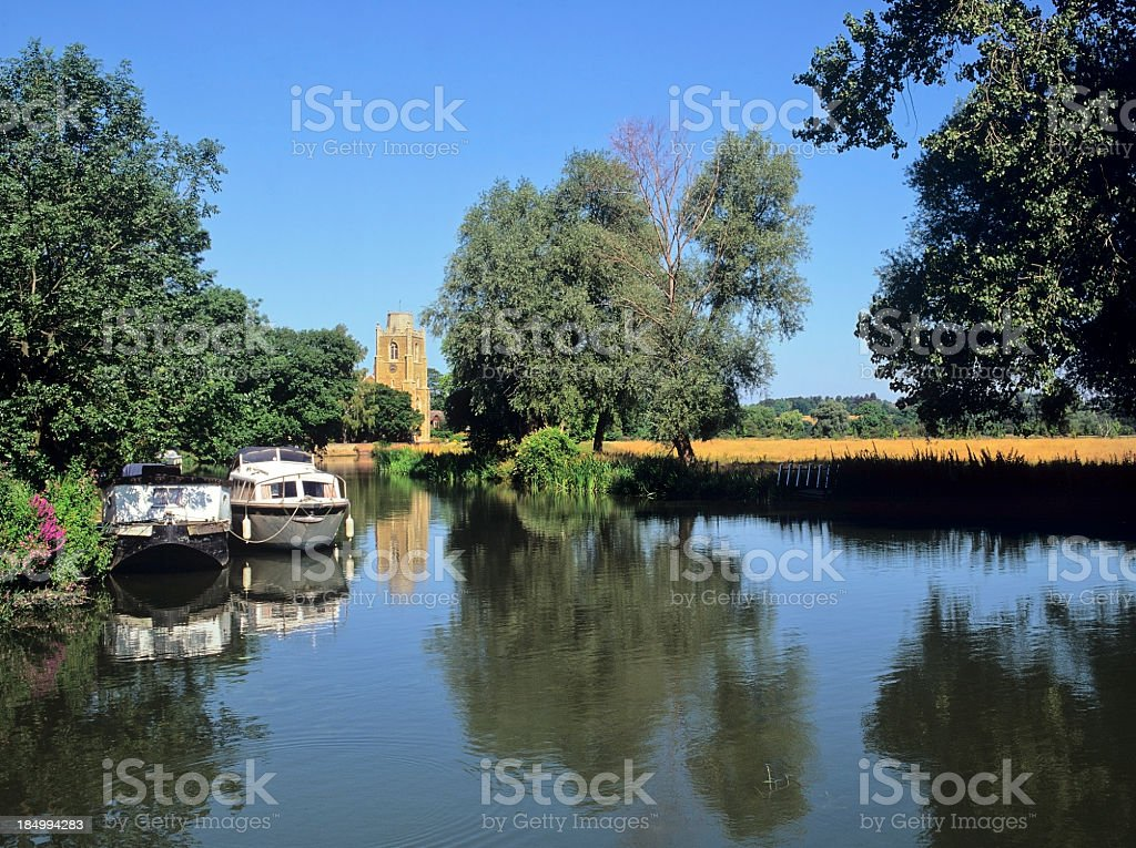 Two houseboats on river surrounded by fields stock photo