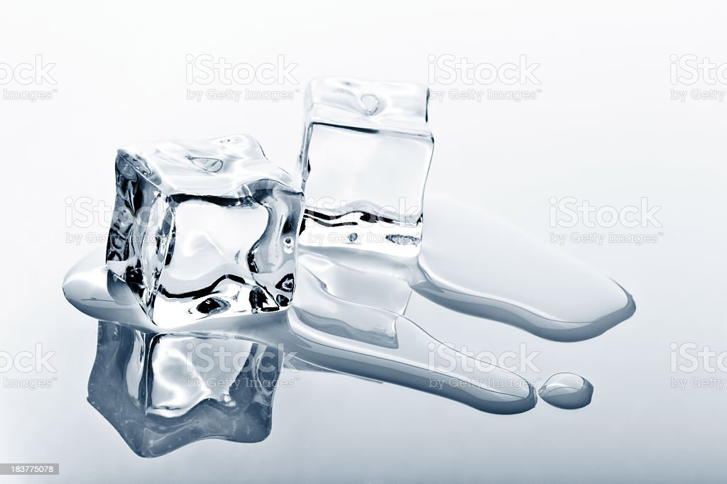 Two ice cubes melting on reflected surface stock photo