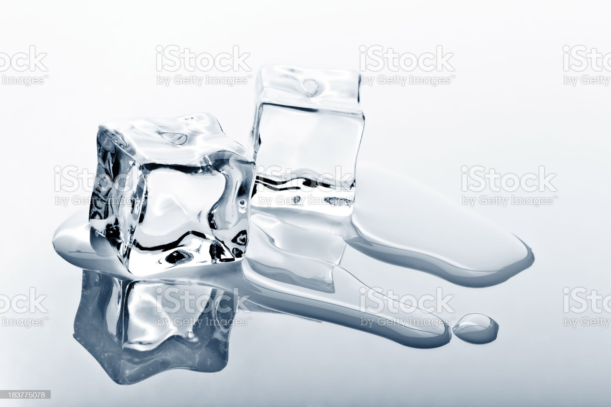 Two ice cubes melting on reflected surface royalty-free stock photo