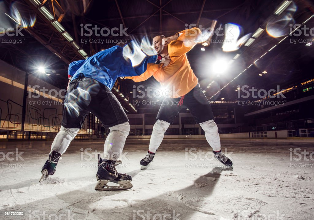 Two ice hockey players fighting in ice hockey rink. stock photo