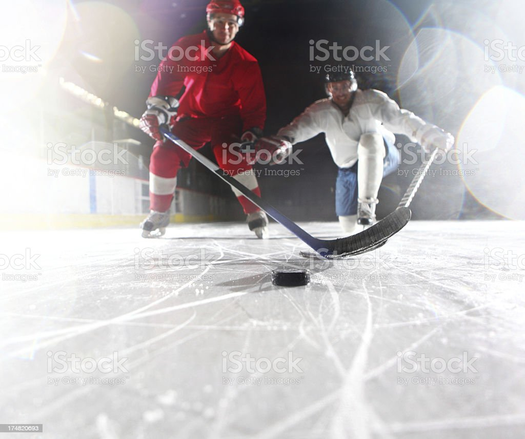 Two ice hockey players reaching for puck royalty-free stock photo