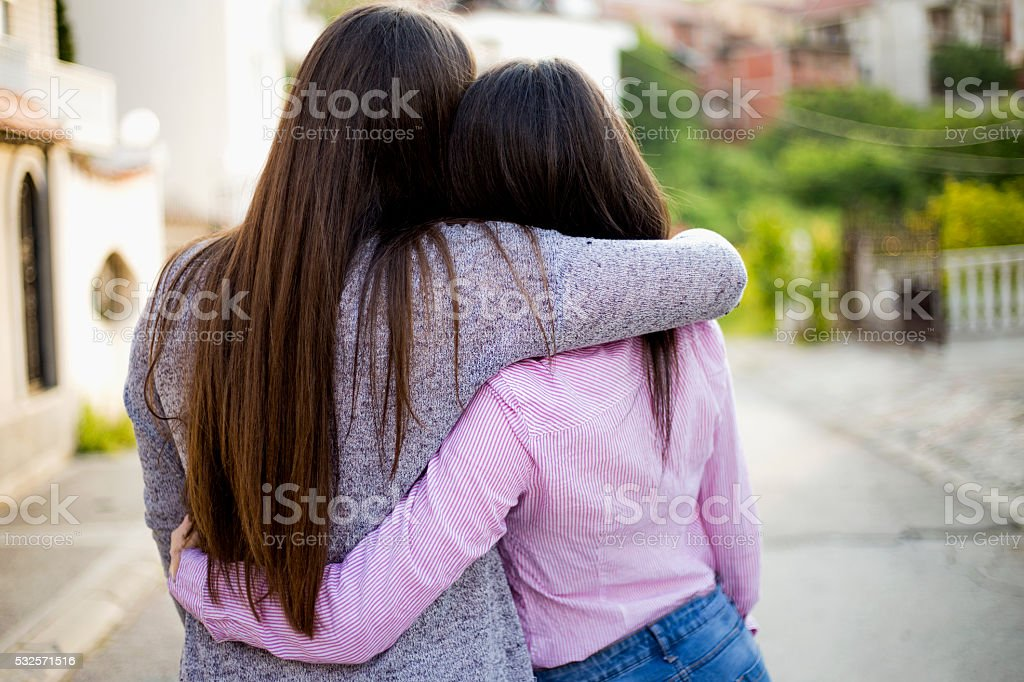 Two identical teenage girlfriends, shot from back stock photo