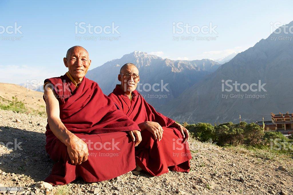 Two Indian Tibetan monks are sitting on a mountain stock photo