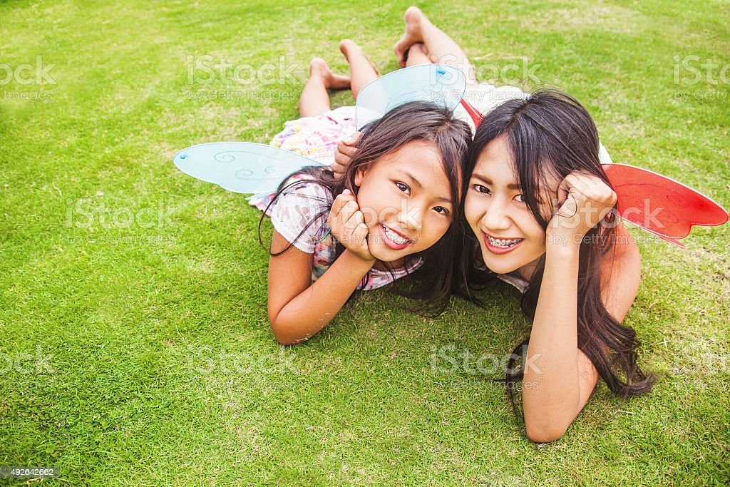 two indonesian sisters lying down on a grass stock photo