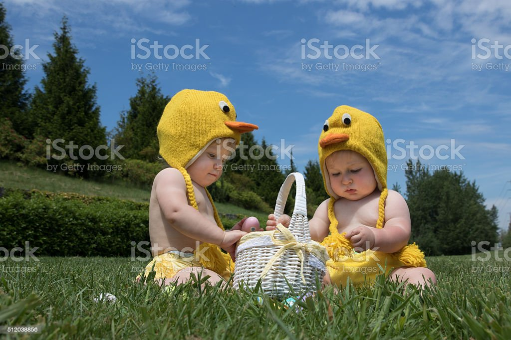 Two infant babies in Easter chicken costumes playing with eggs stock photo