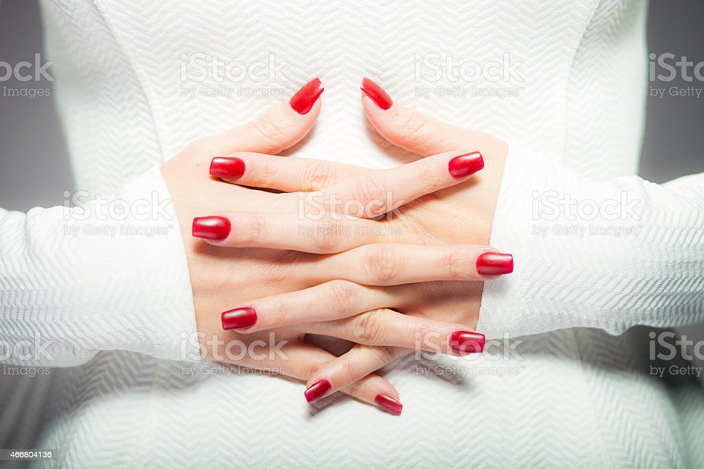 Two interlaced hands with red nails stock photo