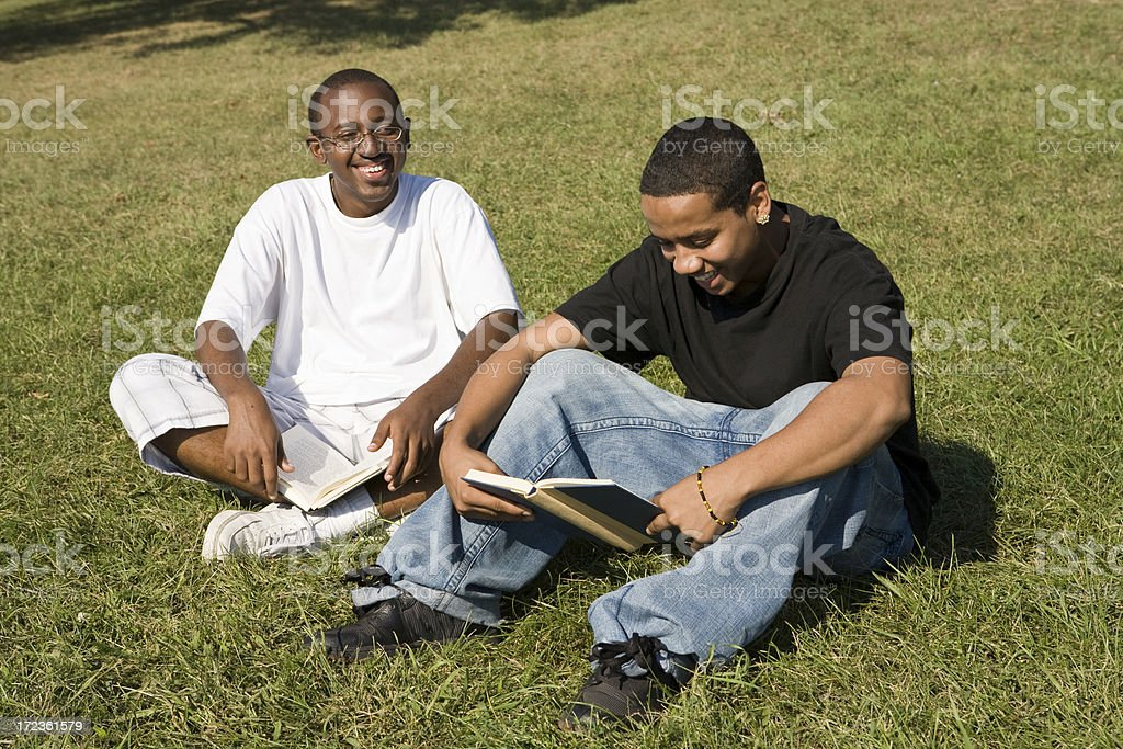 Two interracial students studying and laughing stock photo