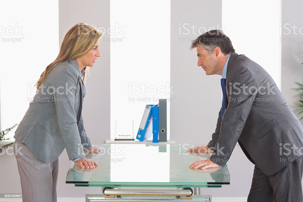 Two irritated businesspeople arguing on each side of a desk stock photo