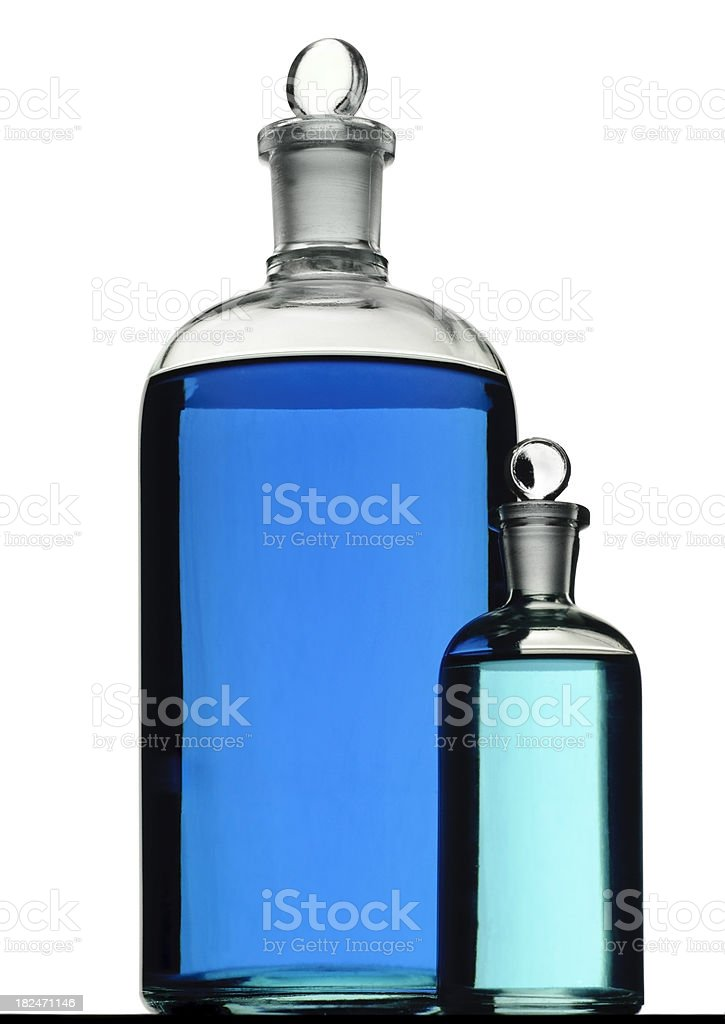 Two Isolated Laboratory Bottles Filled with Blue Chemical Solution royalty-free stock photo