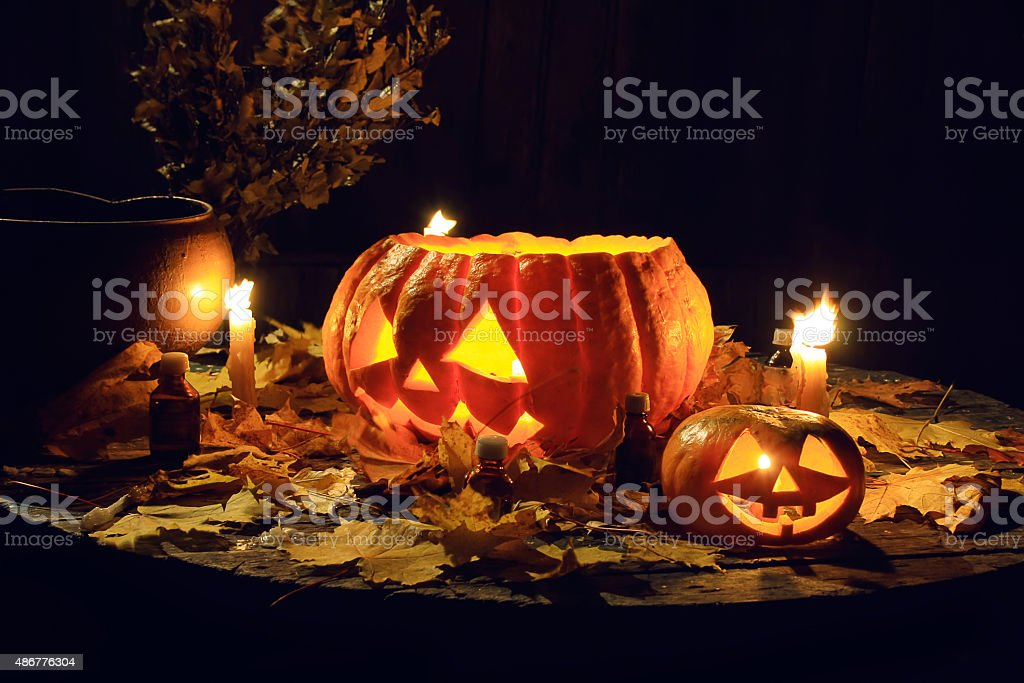 Two jack-o'-lantern on an old wooden table at night. stock photo