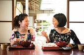Two Japanese friends in restaurant eating noodles