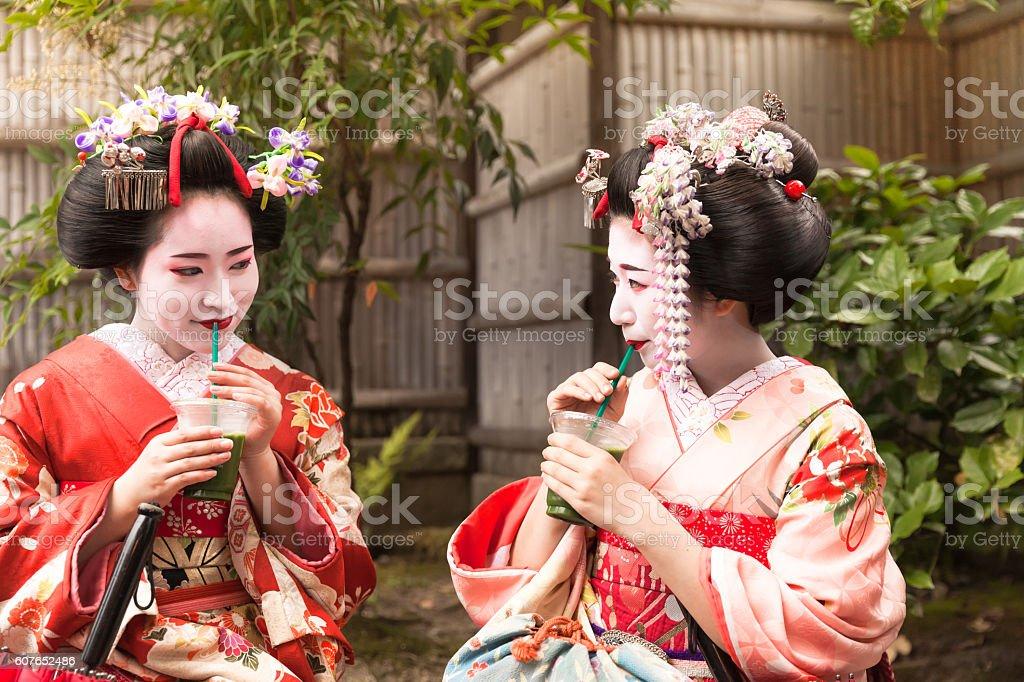 two japanese geisha relaxing drinking ice tea stock photo