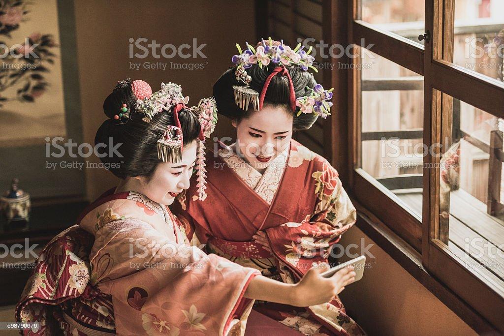 Two Japanese maiko in kimonos using smartphone to take selfie stock photo