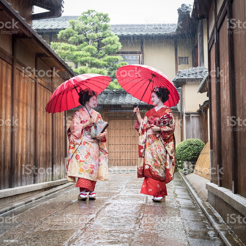 Two Japanese maiko walking in traditional street with umbrellas stock photo