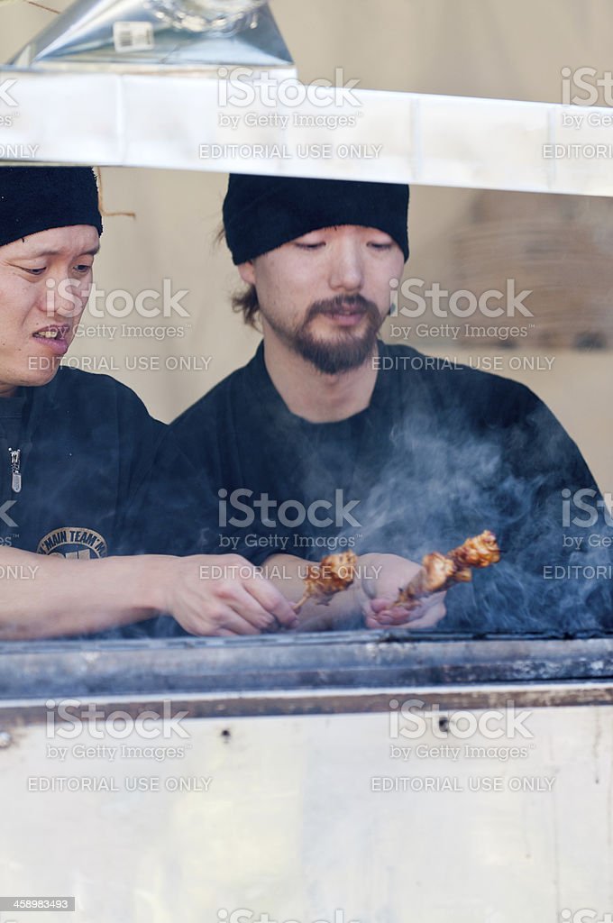Two Japanese Men Barbequing Yakitori at an Outdoor Food Stall royalty-free stock photo
