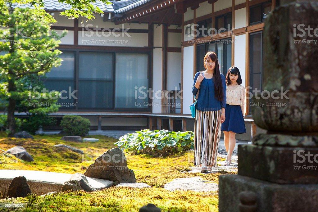 Two Japanese tourists through a temple garden stock photo