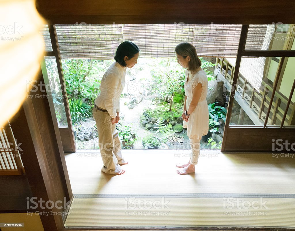 Two Japanese women bowing with respect in a traditional house stock photo