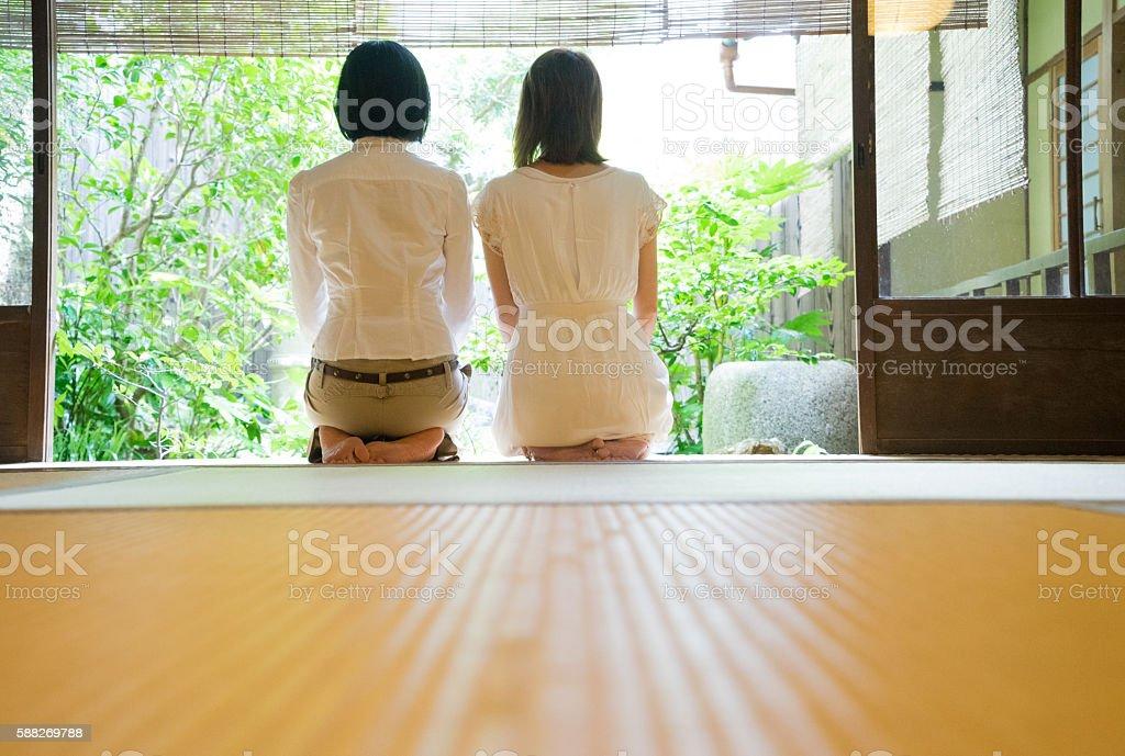 Two Japanese women contemplating the garden from the veranda stock photo