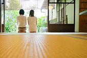 Two Japanese women contemplating the garden from the veranda