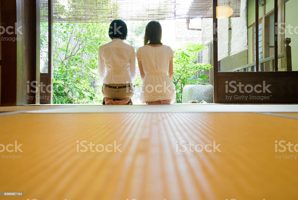 Two Japanese women contemplating the garden from the veranda stock photo