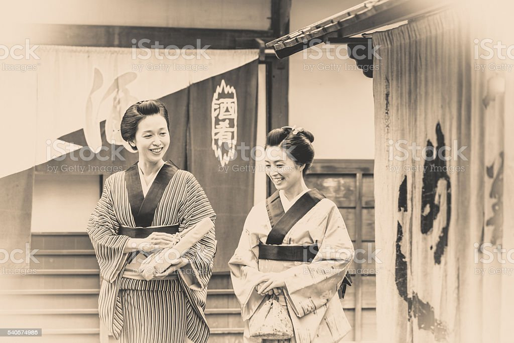 Two Japanese women dressed traditionally, talking a stroll. stock photo