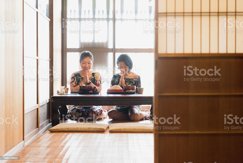 Two Japanese women in give thanks before eating meal stock photo