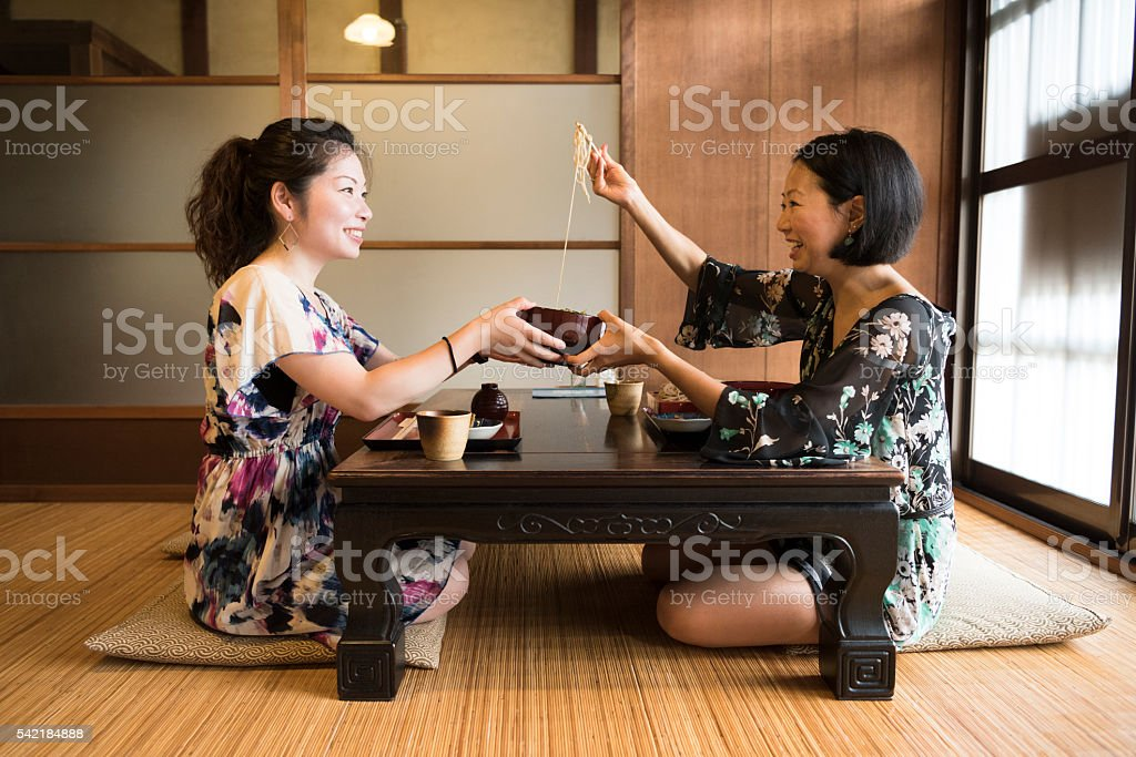 Two Japanese women in restaurant, one serving food stock photo