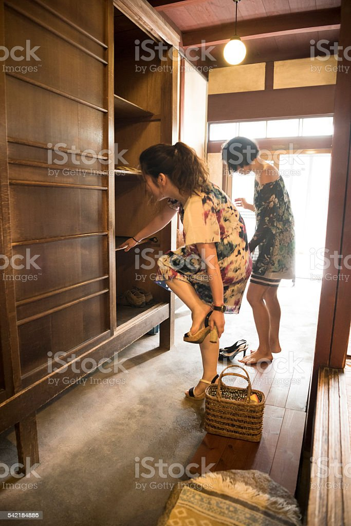 Two Japanese women removing shoes in restaurant entrance stock photo